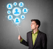 Businessman holding social network balloon Stock Images