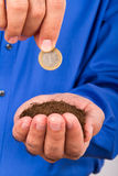 Businessman Holding Soil and Coin Stock Photo