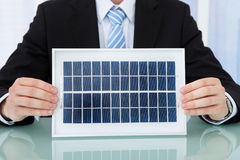 Businessman Holding Solar Panel At Office Desk Royalty Free Stock Images