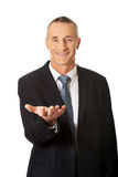 Businessman holding something on his palm Royalty Free Stock Photos