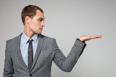 Businessman holding something imaginary in his hand and l Royalty Free Stock Photography