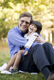 Businessman holding son on grass Royalty Free Stock Photos