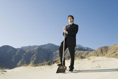 Businessman Holding Spade In Desert Stock Photos