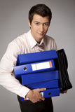 Businessman holding a stack of binders Royalty Free Stock Images