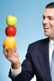 Businessman holding a stack of fruit Stock Image