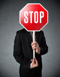 Businessman holding a stop sign. Businessman standing and holding a stop sign in front of his head Stock Image