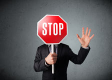 Businessman holding a stop sign. Businessman standing and holding a stop sign in front of his head Royalty Free Stock Images