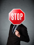 Businessman holding a stop sign. Businessman standing and holding a stop sign in front of his head Stock Photo