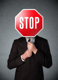Businessman holding a stop sign. Businessman standing and holding a stop sign in front of his head Royalty Free Stock Photo