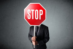 Businessman holding a stop sign. Businessman standing and holding a stop sign in front of his head Royalty Free Stock Image