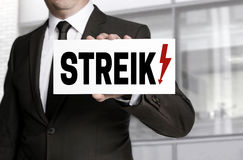 Businessman holding strike sign to viewer stock photography