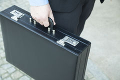 Businessman holding a suitcase royalty free stock photography