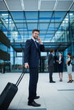 Businessman holding suitcase talking on mobile phone Royalty Free Stock Images
