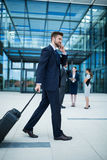 Businessman holding suitcase talking on mobile phone Royalty Free Stock Photography