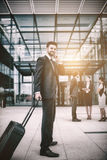 Businessman holding suitcase talking on mobile phone. In office premises Royalty Free Stock Images