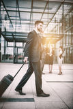 Businessman holding suitcase talking on mobile phone. In office premises Stock Photography