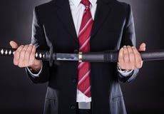 Businessman holding sword Stock Image