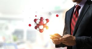 Businessman holding a tabalet with a bunch of spheres levitating above. Mixed media royalty free stock images