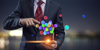 Businessman holding a tabalet with a bunch of spheres levitating above. Mixed media stock images