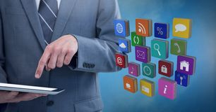 Businessman holding tablet with apps icons with blue foggy background Royalty Free Stock Photos