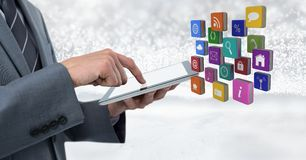Businessman holding tablet with apps icons with bright sparkling star spangled background Stock Photo
