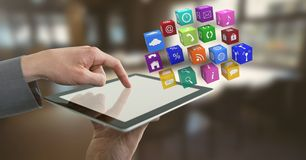 Businessman holding tablet with apps icons in office Stock Images