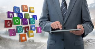 Businessman holding tablet with apps icons outside in landscape Royalty Free Stock Photo