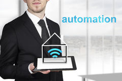 Businessman holding tablet automation. Businessman in black suit holding tablet pc with house symbol and automation royalty free stock images