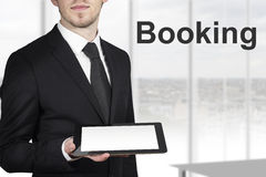 Businessman holding tablet booking Stock Photos