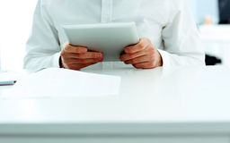 Businessman holding a tablet computer and sitting at the table Royalty Free Stock Photos