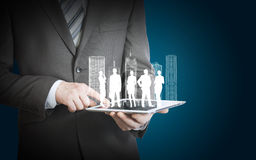 Businessman holding tablet with 3d model of city. And businesspeople silhouette Stock Photography