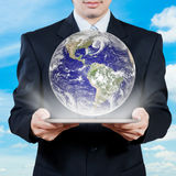 Businessman holding tablet displaying earth with sky in backgrou Stock Images