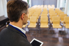 Businessman holding tablet in empty conference hall. Back view of businessman holding tablet and standing in empty conference hall Royalty Free Stock Image