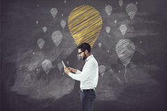 Businessman holding tablet in front of blackboard with balloon Stock Photos