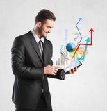 Businessman holding a tablet with growing graphics Royalty Free Stock Photo