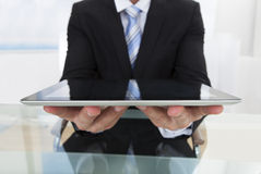 Businessman holding a tablet in his hands. Businessman holding a tablet computer in his hands offering it to the viewer with a smile as he sits at his desk in Royalty Free Stock Photos