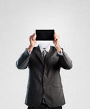 Businessman holding a tablet instead of his head stock photo