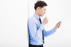 Businessman holding tablet and leaning against white wall Stock Photos