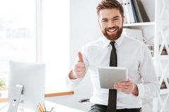 Businessman holding tablet and make thumbs up gesture. Picture of smiling young businessman dressed in white shirt sitting in office holding tablet computer in royalty free stock photography