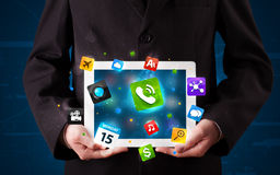 Businessman holding a tablet with modern colorful apps and icons Royalty Free Stock Photo