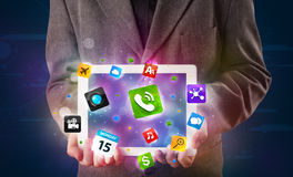 Businessman holding a tablet with modern colorful apps and icons Royalty Free Stock Photos