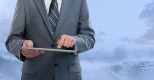 Businessman holding tablet outside in blue landscape Stock Photography