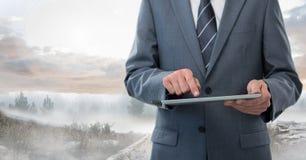 Businessman holding tablet outside in landscape Stock Photo