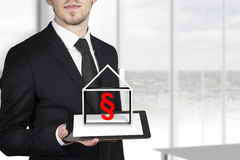 Businessman holding tablet paragraph symbol. Businessman holding tablet pc house red paragraph symbol stock image