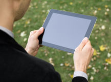 Businessman Holding A Tablet PC. Businessman in a park holding a blank touch screen device Stock Photos