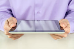 Businessman Holding Tablet PC. Closeup shot of businessman hands are holding digital tablet pc. Shallow depth of field on fingers Stock Images