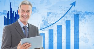 Businessman holding tablet PC against graphs. Digital composite of Businessman holding tablet PC against graphs Royalty Free Stock Photography
