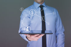 Businessman holding a tablet pc with dollar icons. Internet and business concept. Stock Photo