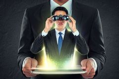 Businessman holding tablet pc and out man with binoculars Stock Photos