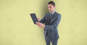 Businessman holding tablet PC over colored background. Digital composite of Businessman holding tablet PC over colored background royalty free stock photo